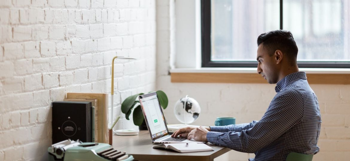 Manager typing on laptop at home desk while managing a workforce that is working from home.