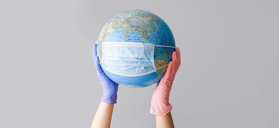 Person wearing rubber gloves holding up globe with mask on it